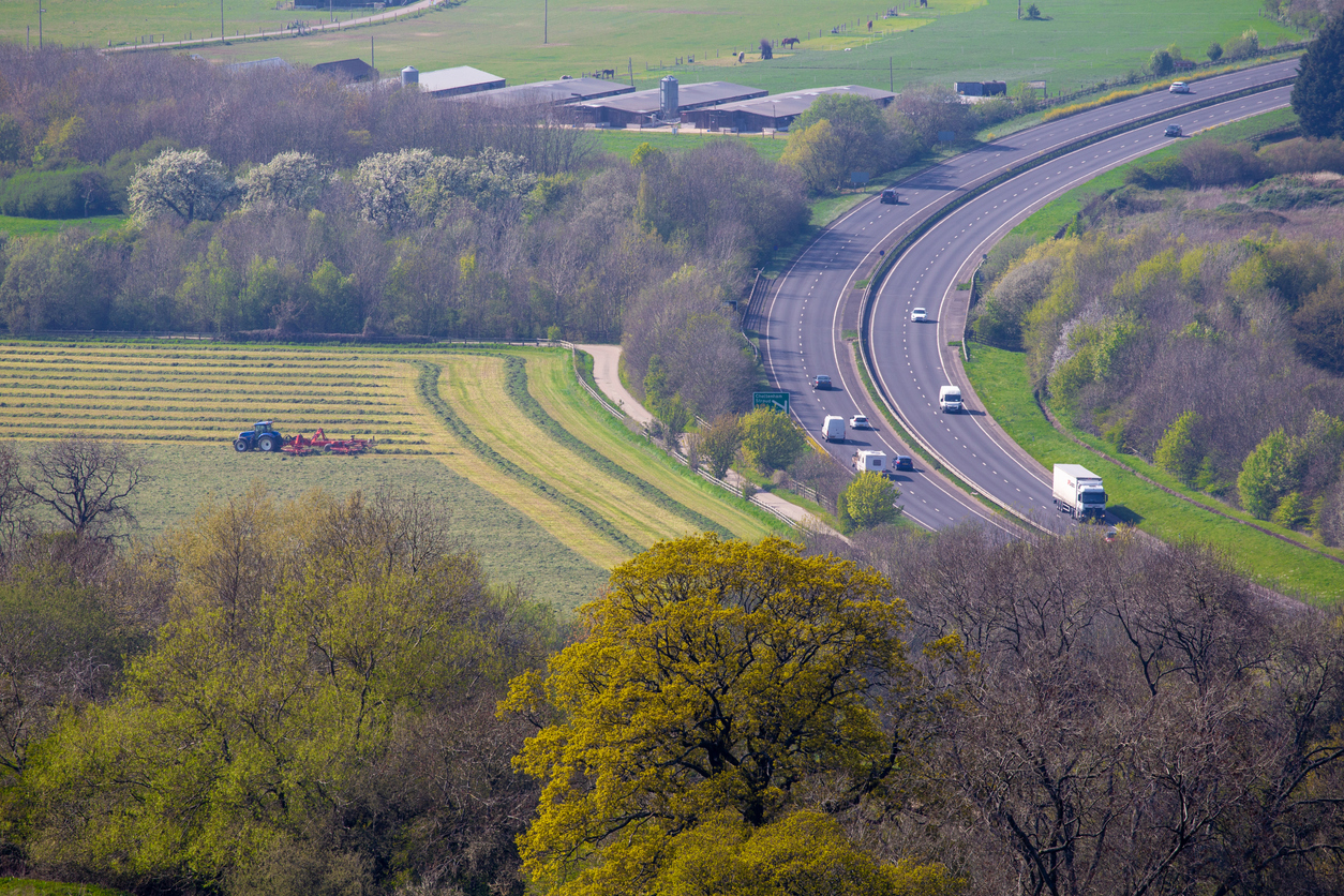 Elevated view of a dual carriageway slicing through the Cotswold landscape - highlighting the environmental problems with traffic pollution and  road infrastructure